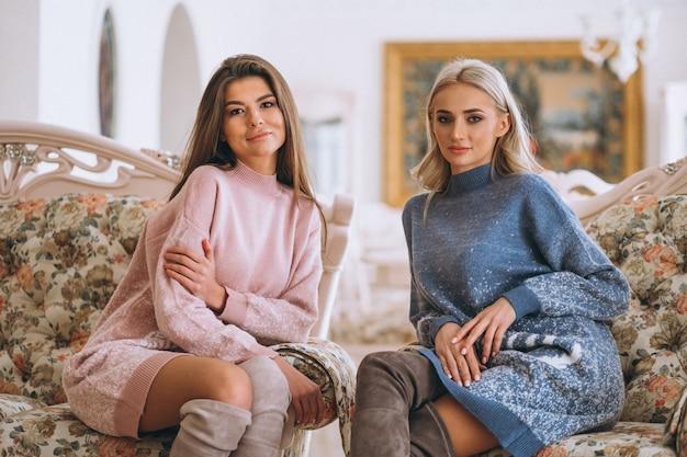 Zwei mädchen, die auf sofa sitzen und plaudern Kostenlose Fotos