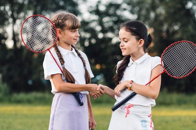 Zwei mädchen, die badminton rütteln hände mit einander halten Kostenlose Fotos