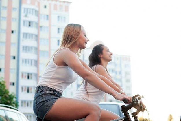 Zwei mädchen, die einen perfekten abend in ihren fahrrädern Kostenlose Fotos