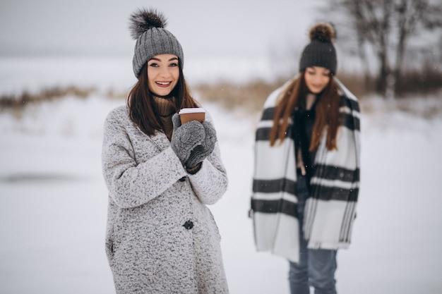 Zwei mädchen, die zusammen in einen winterpark gehen Kostenlose Fotos