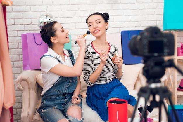 Zwei mädchen halten pinsel und parfüm zur kamera Premium Fotos