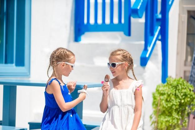 Zwei mädchen in blauen kleidern sitzen auf blauen stühlen Premium Fotos
