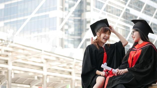 Zwei mädchen in den schwarzen kleidern und halten die diplombescheinigung, die mit glücklichem absolvent sitzt und lächelt. Premium Fotos