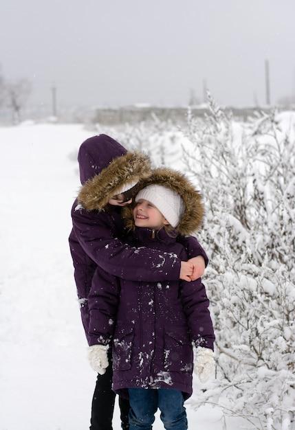 Zwei mädchen in identischen jacken stehen und plaudern bei schneefall auf einem schneebedeckten feld, schauen sich an und lächeln Premium Fotos