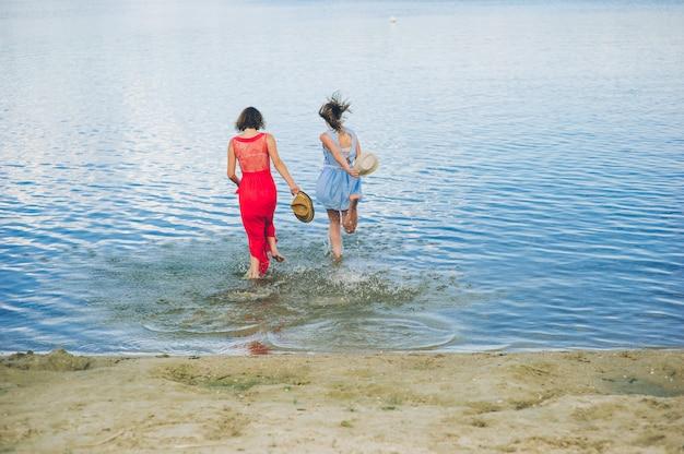Zwei mädchen laufen ins wasser Premium Fotos
