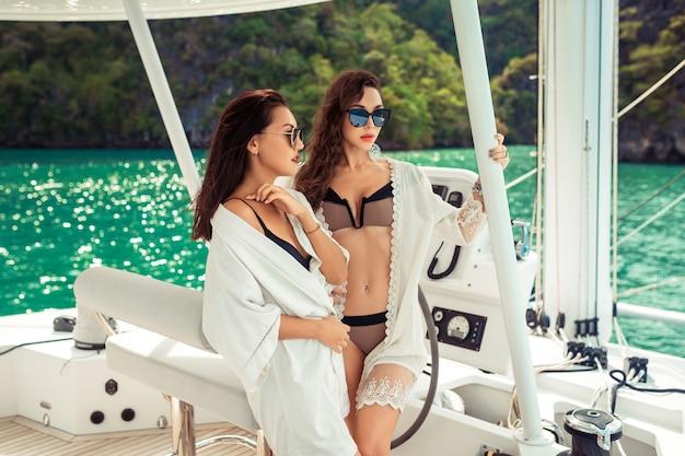 Zwei mädchen leiten die yacht. sommerkreuzfahrt yacht. freunde reisen mit der yacht auf dem meer. urlaub auf einer yacht. rückansicht Premium Fotos