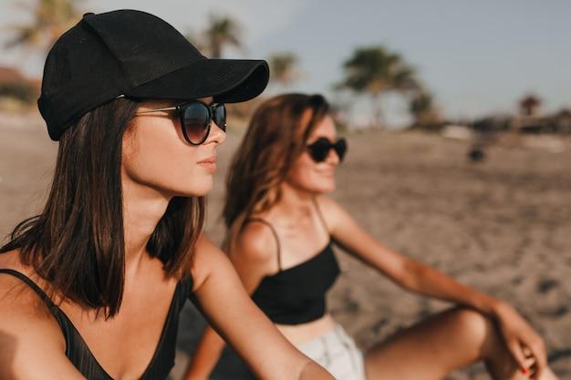 Zwei mädchen mit sonnenbrille und badeanzug sitzen am sandstrand mit palmen und schauen mit romantischem lächeln auf den ozean. zwei beste freundinnen verbringen urlaub in den tropen Kostenlose Fotos