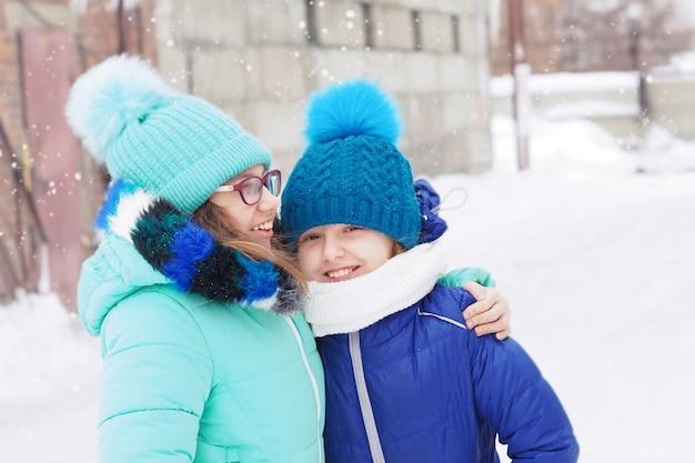 Zwei mädchen schwestern im winter auf den straßen in jacken und hüten lachen und umarmen. schneit. Premium Fotos