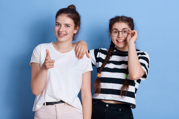 Zwei mädchen sehen glücklich aus, zeigen und schauen mit positivem ausdruck, damen, die in stilvollen kleidern isoliert stehen. Kostenlose Fotos