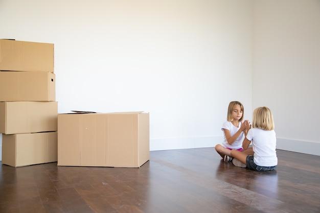 Zwei mädchen sitzen auf dem boden in der nähe von kistenhaufen in ihrer neuen wohnung und spielen zusammen Kostenlose Fotos