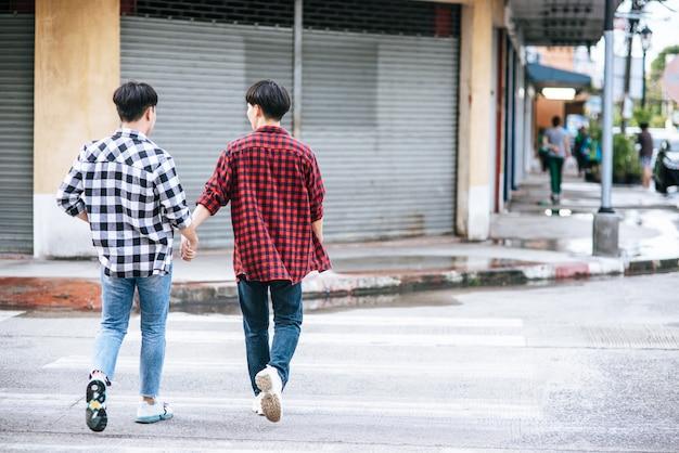 Zwei männer, die sich lieben, halten sich an den händen und gehen zusammen. Kostenlose Fotos