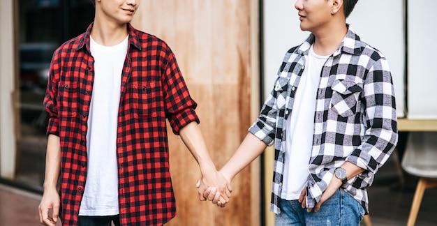 Zwei männer, die sich lieben, stehen hand in hand. Kostenlose Fotos