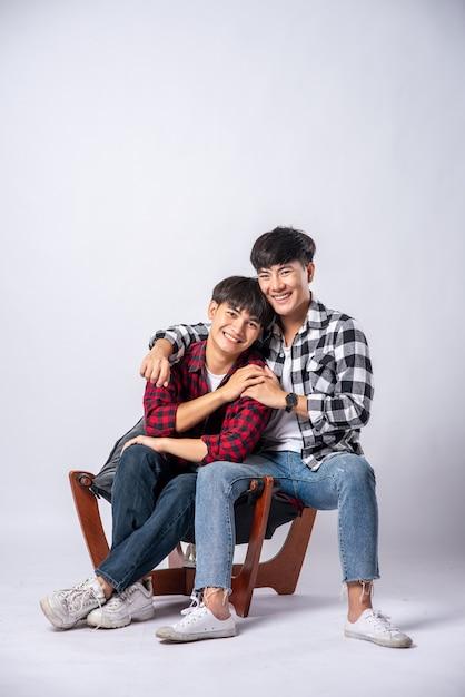 Zwei männer, die sich lieben, umarmen sich und setzen sich auf einen stuhl. Kostenlose Fotos