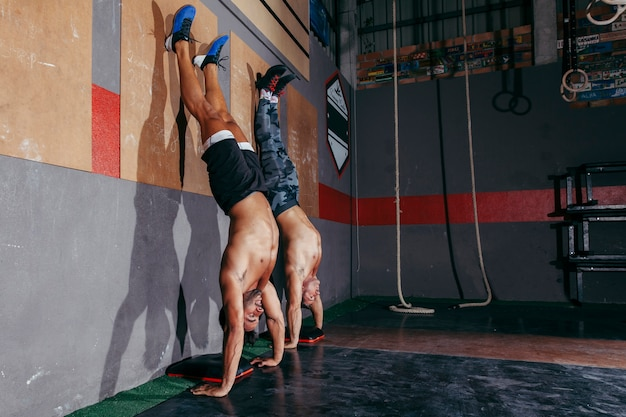 Zwei männer machen handstand im fitnessstudio Kostenlose Fotos
