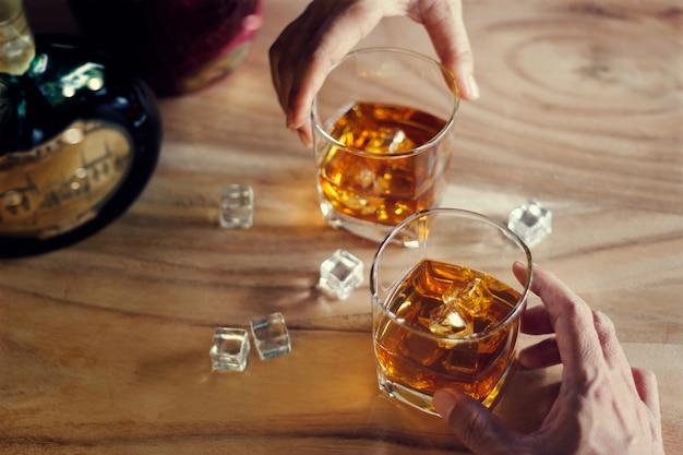 Zwei männer stoßen an, wenn sie ein glas whisky trinken Premium Fotos