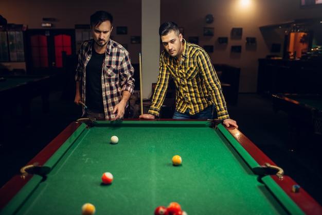 Zwei männliche billardspieler mit queue, poolraum Premium Fotos