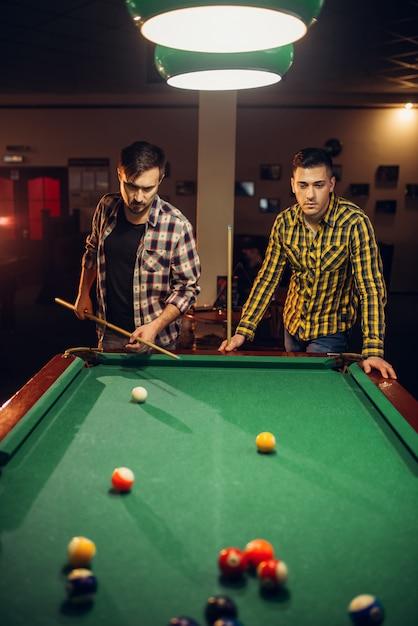 Zwei männliche billardspieler mit stichwort am tisch mit bunten bällen, poolraum. männer spielen amerikanisches poolspiel in der sportbar Premium Fotos