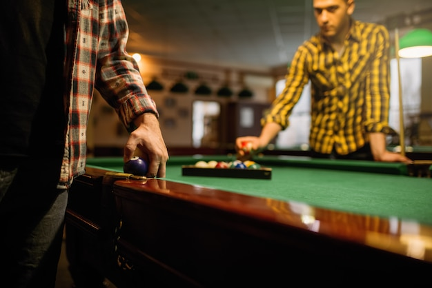 Zwei männliche billardspieler platzieren bunte bälle, poolraum. männer spielen amerikanisches poolspiel im sportverein Premium Fotos