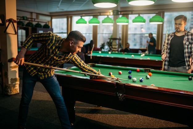 Zwei männliche billardspieler verbringen zeit im poolraum. männer spielen amerikanisches poolspiel im sportverein Premium Fotos