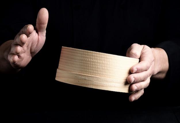 Zwei männliche chefhände halten ein rundes hölzernes sieb Premium Fotos