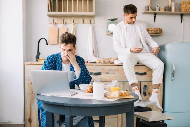 Zwei männliche freunde, die laptop und handy zur zeit der frühstückionenküche verwenden Kostenlose Fotos