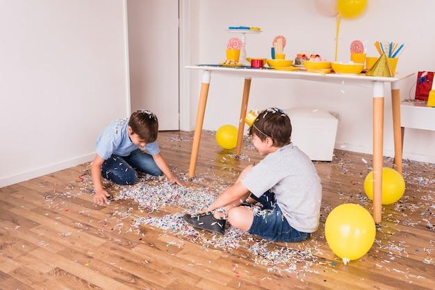 Zwei männliche freunde, die zu hause mit konfetti in der partei spielen Kostenlose Fotos