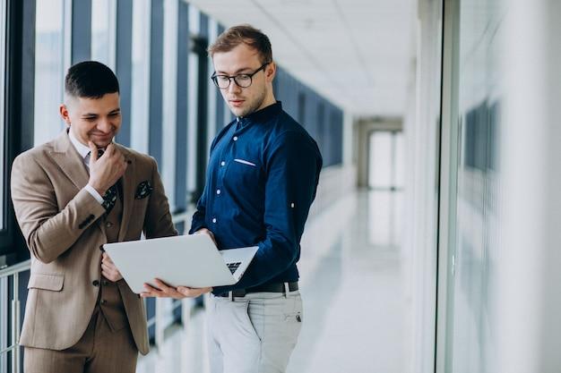 Zwei männliche kollegen im büro, stehend mit laptop Kostenlose Fotos