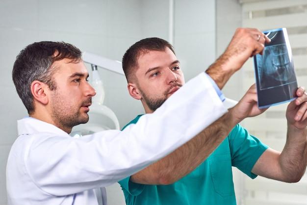 Zwei männliche zahnärzte, die röntgenstrahl analysieren Premium Fotos