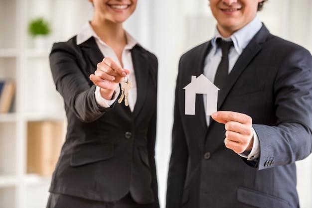Zwei makler in anzügen zeigen ein modell von haus und schlüssel. Premium Fotos