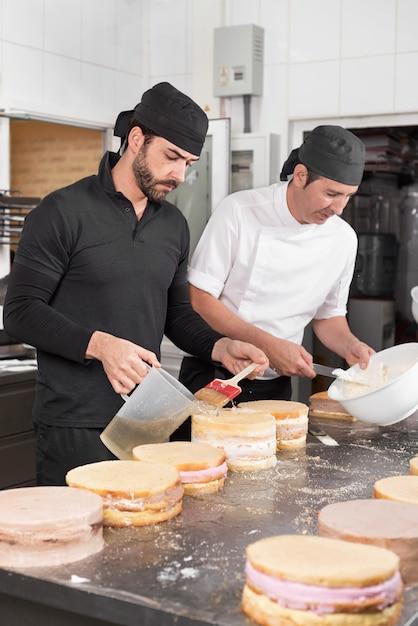 Zwei-mann-konditoren, die kuchen an der konditorei zusammenarbeiten. Premium Fotos