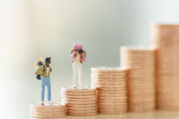 Zwei mann und frau miniaturreisende figuren mit rucksack stehen auf stapel von münzen Premium Fotos