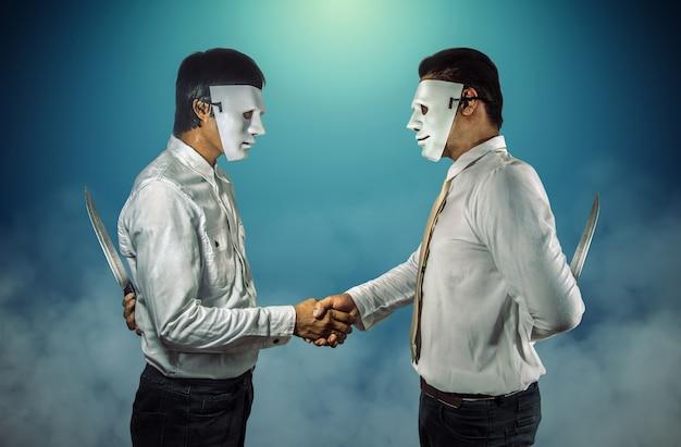 Zwei maskierte geschäftsleute, die sich die hand geben und messer hinter dem rücken halten. Premium Fotos