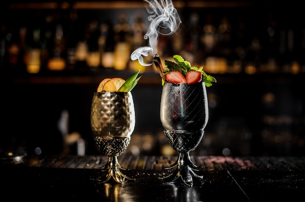 Zwei metallgläser frische sommercocktails verziert mit frucht auf der bar theke Premium Fotos