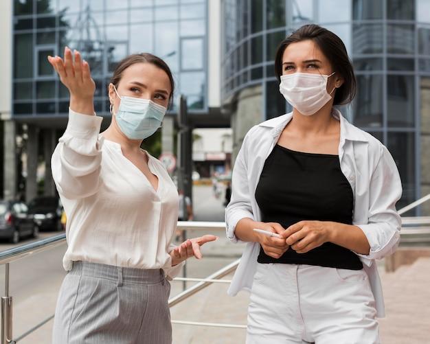 Zwei mitarbeiter im freien während der pandemie tragen masken Kostenlose Fotos
