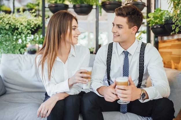 Zwei mitarbeiter kommunizieren in einer pause in einem intelligenten raum. in weißen hemden gekleidet. latte in ihren händen. Premium Fotos
