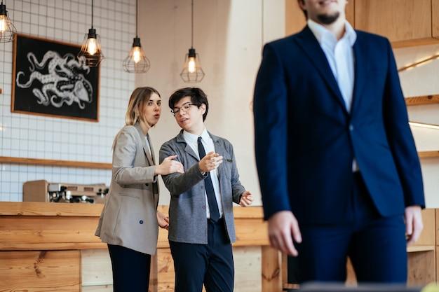Zwei mitarbeiter starren und klatschen über ihren männlichen kollegen im büro Kostenlose Fotos