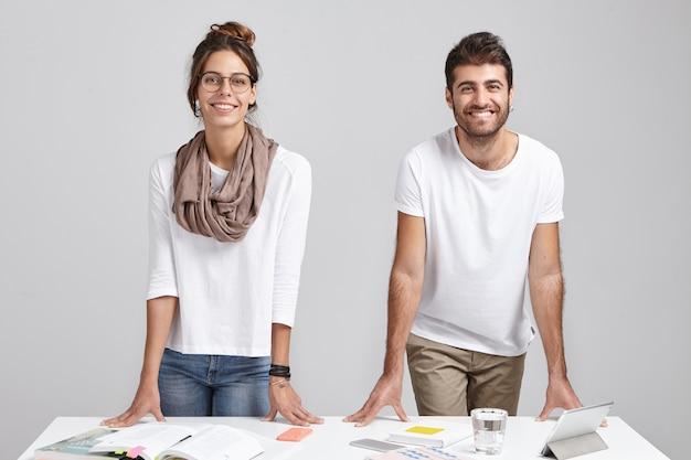 Zwei mitarbeiter stehen im modernen büro am tisch mit dokumenten und tablette Kostenlose Fotos