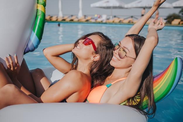 Zwei modelle, die auf dem schwimmer im schwimmbad abkühlen. sie tragen badeanzüge und sonnenbrillen. erstes modell chillen und die augen geschlossen halten. zweitens streckt man die arme und lächelt. sie sind entspannt und sexy. Premium Fotos