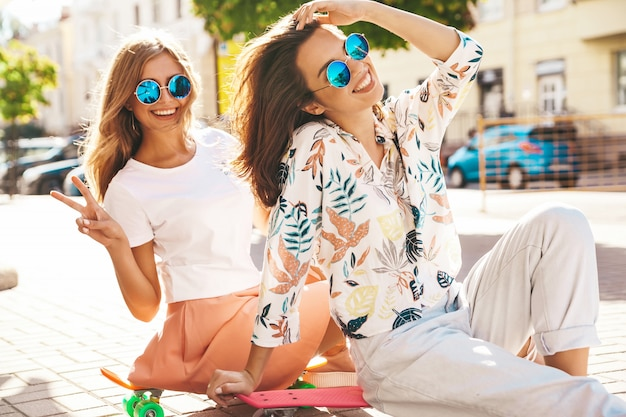 Zwei modelle im sonnigen sommertag in der hipster-kleidung, die auf penny skateboard auf der straße sitzt Kostenlose Fotos