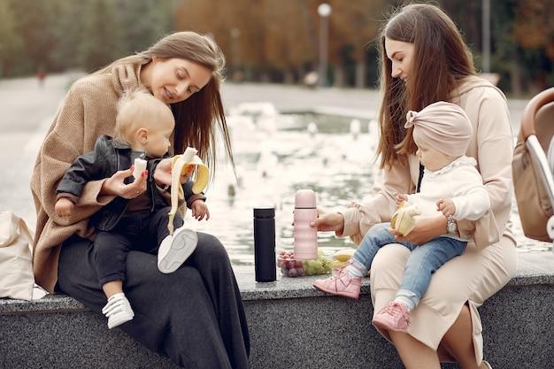 Zwei mütter mit kleinen kindern verbringen zeit in einem park Kostenlose Fotos