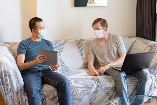 Zwei multiethnische männer mit maske als freunde, die technologie einsetzen und zu hause in quarantäne sprechen Premium Fotos