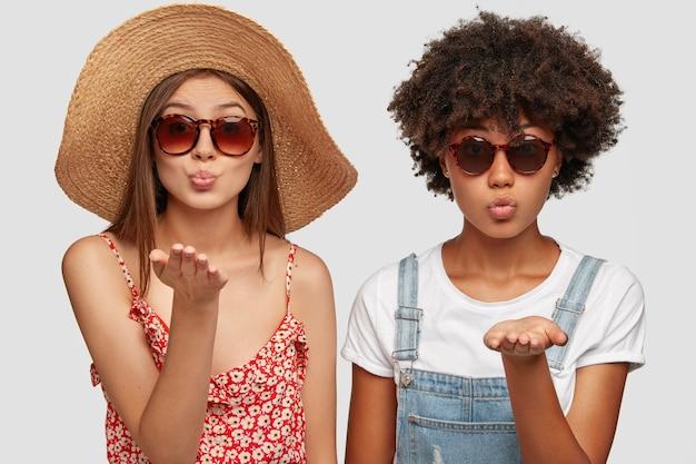Zwei multiethnische schwestern blasen airkiss in die kamera, tragen trendige sonnenbrillen und sommerkleidung Kostenlose Fotos