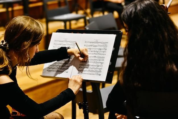 Zwei musikerinnen, die eine partitur mit einem bleistift korrigieren, bevor das orchester zu spielen beginnt. Premium Fotos