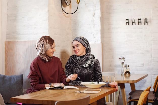 Zwei muslimische geschäftsfrauen trafen sich in einem café und diskutierten über arbeitsmomente, in denen sie alles in ein notizbuch schrieben Premium Fotos