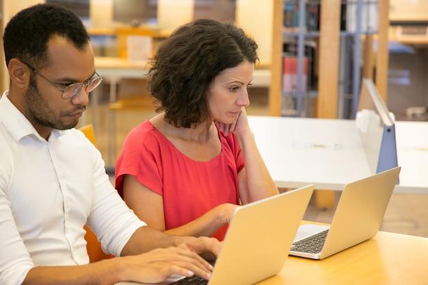 Zwei nachdenkliche menschen sitzen mit laptops in der bibliothek Kostenlose Fotos