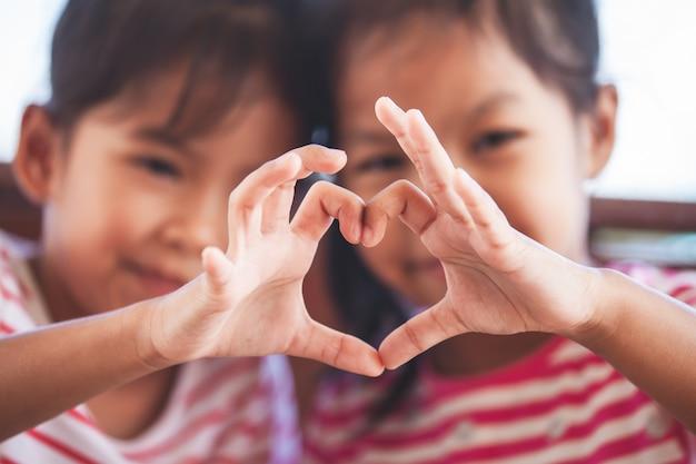Zwei nette asiatische kindermädchen, die herzform mit den händen zusammen mit liebe bilden Premium Fotos
