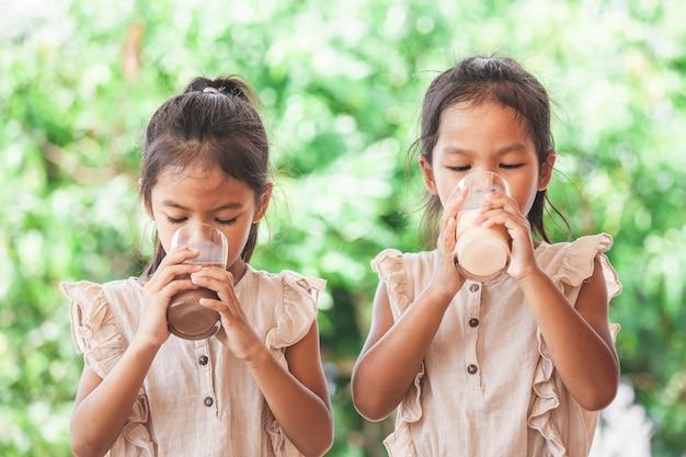 Zwei nette asiatische kindermädchen, die zusammen eine milch vom glas trinken Premium Fotos