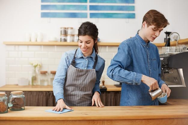 Zwei nette baristas, die an der theke arbeiten und glücklich aussehen. Kostenlose Fotos