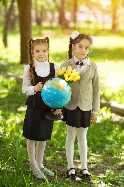 Zwei nette kaukasische mädchenschulmädchen mit blumen und einer kugel Premium Fotos