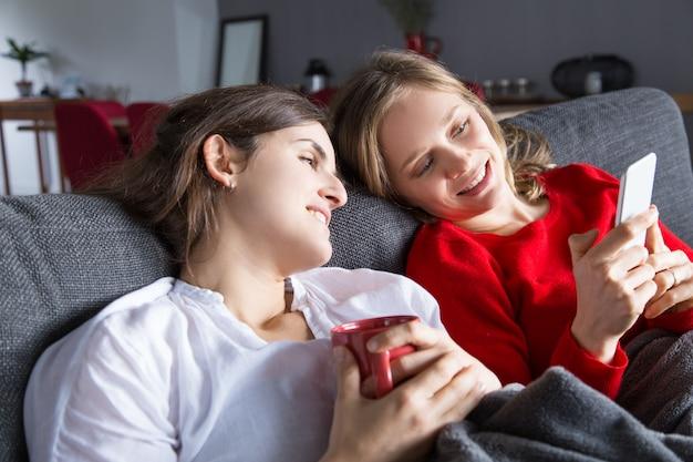 Zwei nette mädchen, die auf couch stillstehen und nettes video genießen Kostenlose Fotos